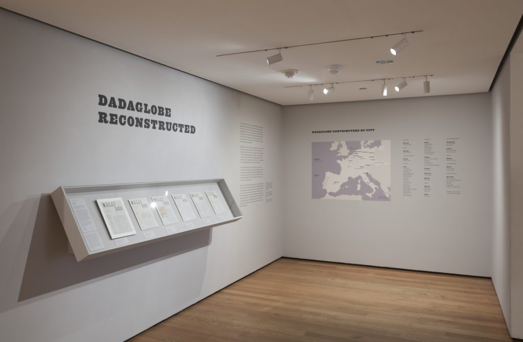 "Opening room to exhibition that includes wall vinyl of the title ""Dadaglobe Reconstructed"" and a map of where participating artists came from."
