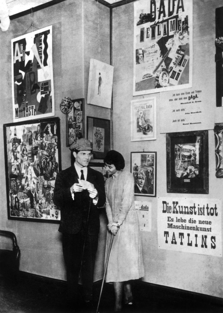 Photograph of Hannah Hoch and Raoul Hausmann at the Dada Fair. To the left is Hannah Hoch's collage Cut with the Kitchen Knife; to the left are Dada slogans on posters:  art is dead love the new machine art TATLINS
