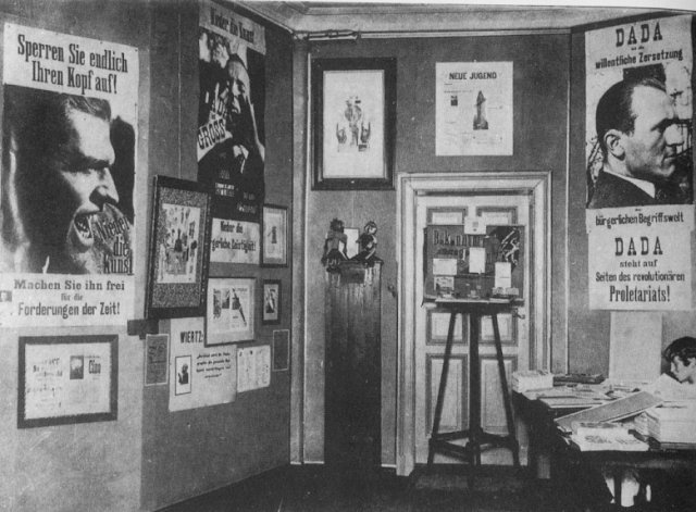 A photograph of the first room of the Dada Fair - there are posters on the wall featuring the faces of the three organisers and Dada slogans in German