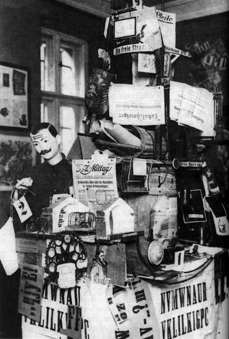 A photograph of an assemblage shown at the Fair. It is made up of newspapers and bric-a-brac, including newspapers and cogs; there is a mustachioed mannequin to the left.