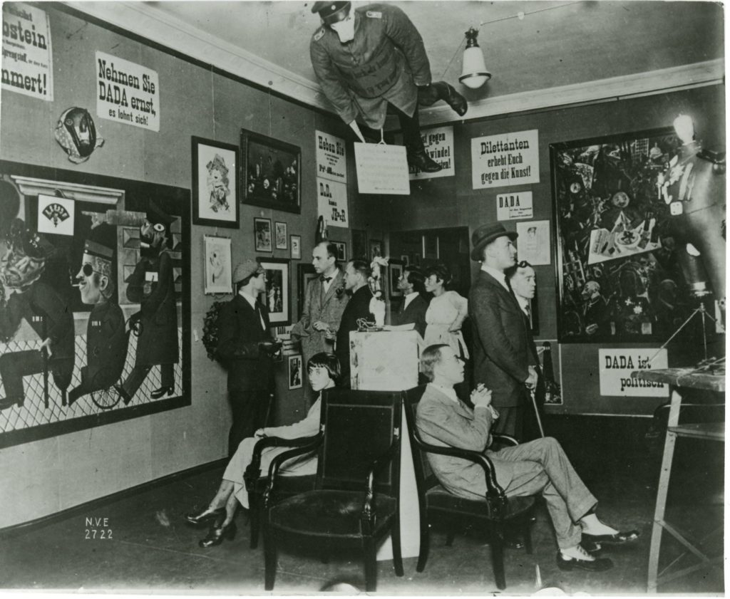 A photograph of the second room of the Dada Fair. A small group of people gathers to look at the work on the walls. There are paintings and posters with Dada slogans in German; above them hangs a mannequin, dressed in soldier's uniform with a pig's head (this is the Prussian Archangel).