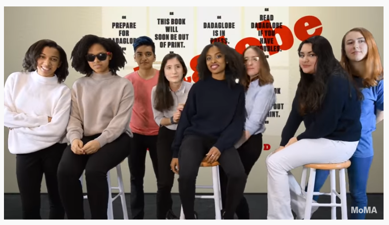 Image still from video that captures all 8 members of the MoMA Teens Digital Advisory Board of 2016 standing in front of a green screen with an archival image of the Dadaglobe project projected on it. 3 members are seated on white stools while the rest are standing in between them.